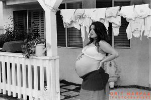 pregnant woman holding belly in front of house
