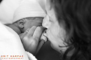 mother kissing new born hand